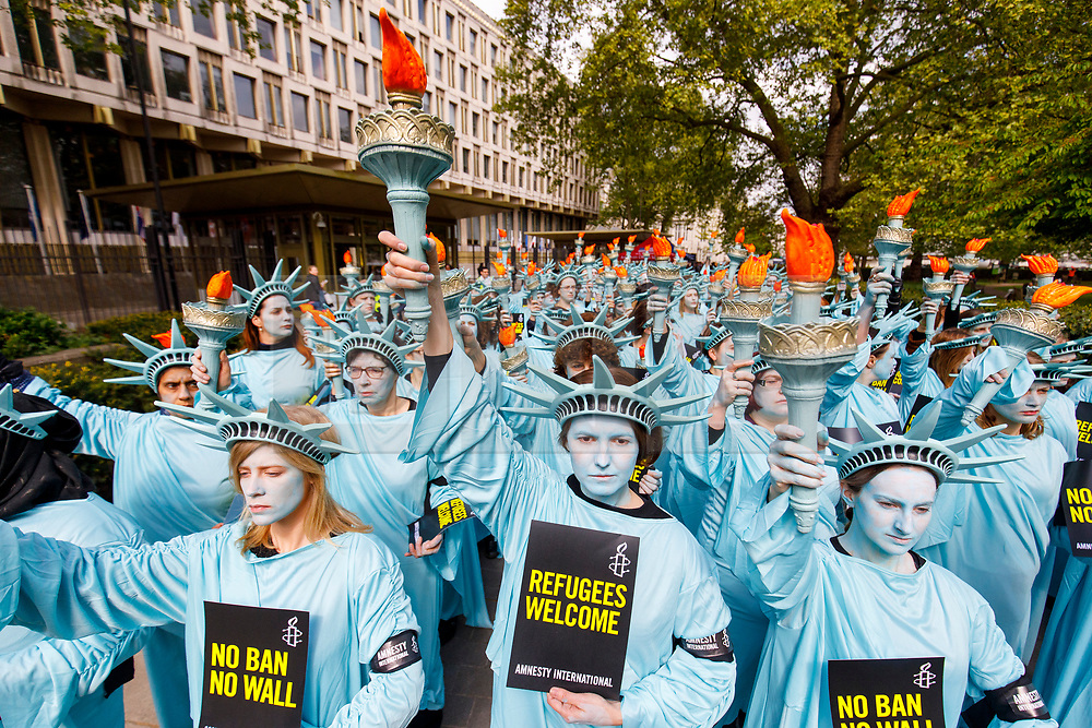 © Licensed to London News Pictures. 27/04/2017. London, UK. One hundred Amnesty International activists dressed as 'Statues of Liberty' protest outside the US Embassy in London on Thursday 27 April 2017 to mark US President Donald Trump's first 100 days in office. Photo credit: Tolga Akmen/LNP
