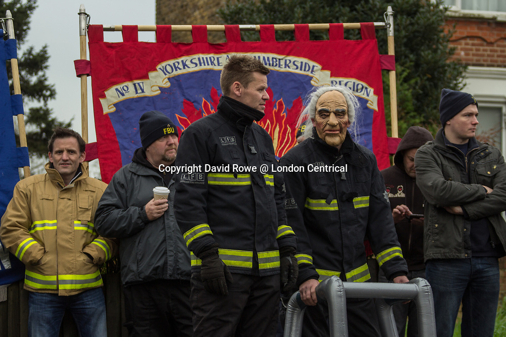 A protester wears a grandad face mask to highlight pension changes that will result in 60 year old fire fighters. The Fire Brigade Union protest at the newly opened fire station was to protest against proposed pension changes.