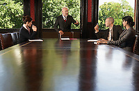 Businesspeople meeting around boardroom table businessman standing