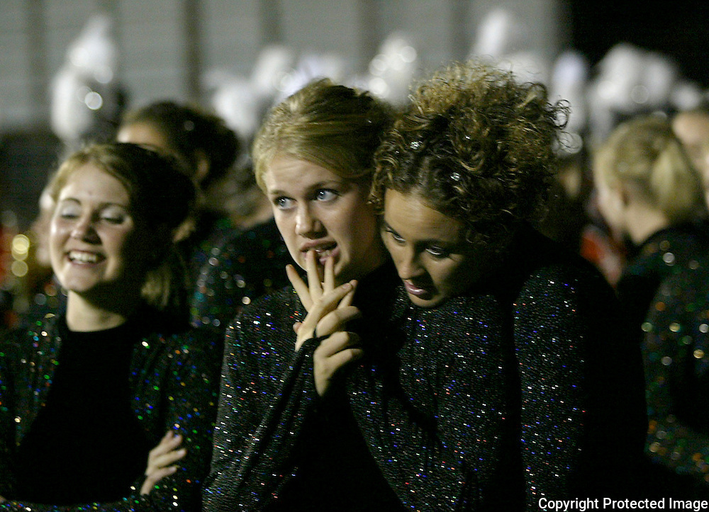 "Color guard captains Alaicia Kuyken, center, and Angela Jiskoot, right, show anxiety as they prepare to take the field in Marshall Mn., for the awards ceremony.  The MOC Floyd Valley band had not lost a competion in two years, but were stuggling with a difficult  program this year.  ""I dreaded standing on the field while they were calling out awards for the other bands,"" said Kuyken.  ""I had never failed in band before,"" said Jiskoot.  ""As a section leader, I felt like I hadn't pushed the other girls enough.  We just have to get better."""