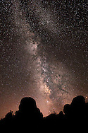 The milky way and galactic core rising above two giant silhouetted boulders at Arches National Park in Moab, Utah.