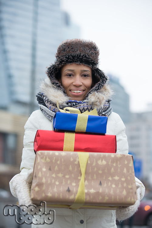 Portrait of happy woman carrying stacked gifts during winter