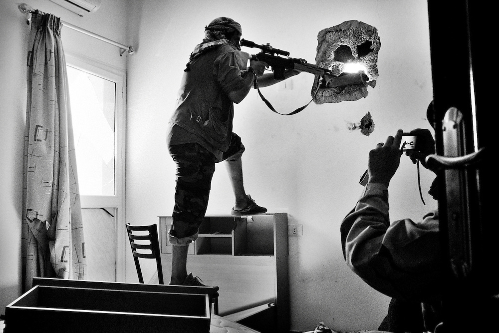 An anti-Qaddafi sniper fires from inside a stormed bedroom at a residential compound during an intense street battle against loyalists to Col. Muammar el-Qaddafi as they advance into the town of Sirte, Libya, on October 15, 2011. Photo by Mauricio Lima for The New York Times
