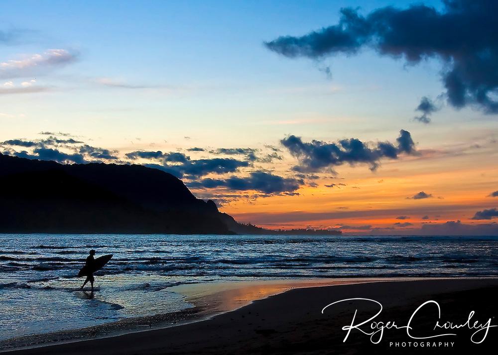 A lone surfer heads home in the sunset on Ke'e Beach at Hanalei Bay on the island of Kaua'i, Hawaii.