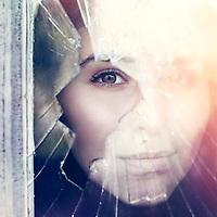 A woman looks through a colourful broken window.