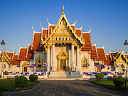 31 MARCH 2015 - BANGKOK, THAILAND: Wat Benchamabophit Dusitvanaram, a Buddhist temple (wat) in the Dusit district of Bangkok, Thailand. Also known as the marble temple, it is one of Bangkok's best known temples and a major tourist attraction. It typifies Bangkok's ornate style of high gables, stepped-out roofs and elaborate finials. Monastic life at Wat Bencha differs from most other temples in that lay people come to the temple to present food and alms to the monks rather than the monks going out and walking through the community as they do at most other Thai temples.     PHOTO BY JACK KURTZ