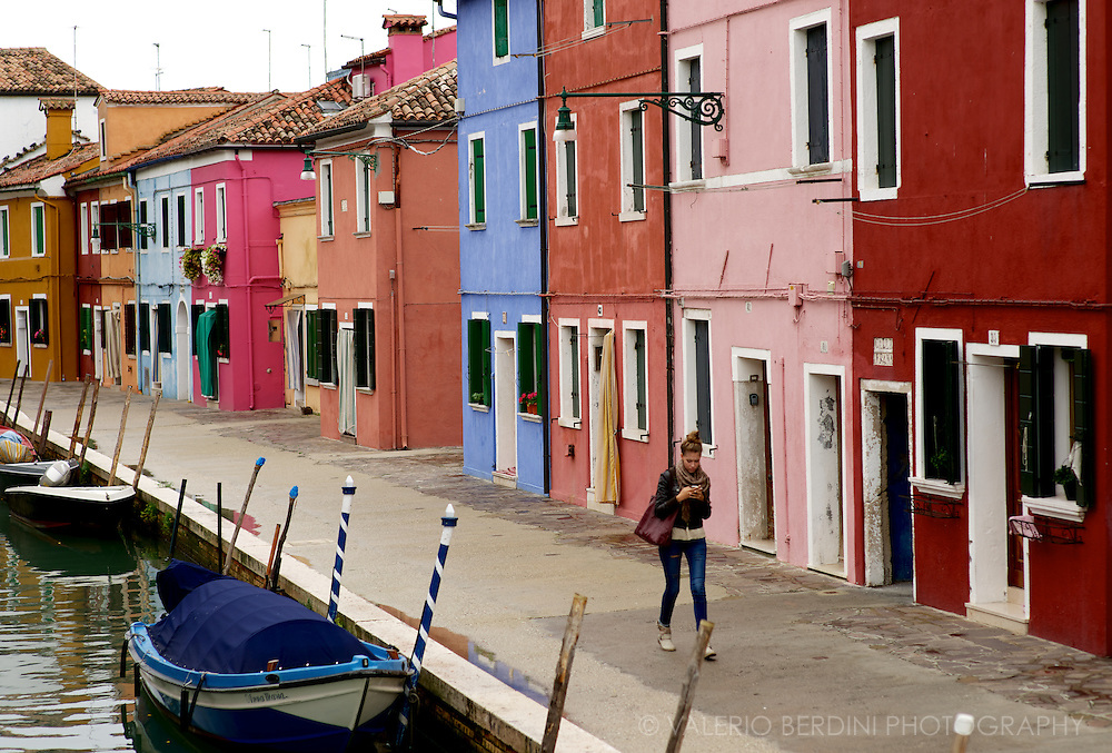 A girl walks along another of the canals of Burano. Part of the Venetian lagoon this tiny archipelago of three islands separated by canals and joined by bridges is renowned for handmade lace (now almost disappeared) and coloured houses.