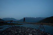 Man walks over a newly built bridge between the villages of Duisi and  Omalo with the Greater Caucasus Mountain Range in the backdrop. The old bridge was washed away in a flood the month before. Republic of Georgia.