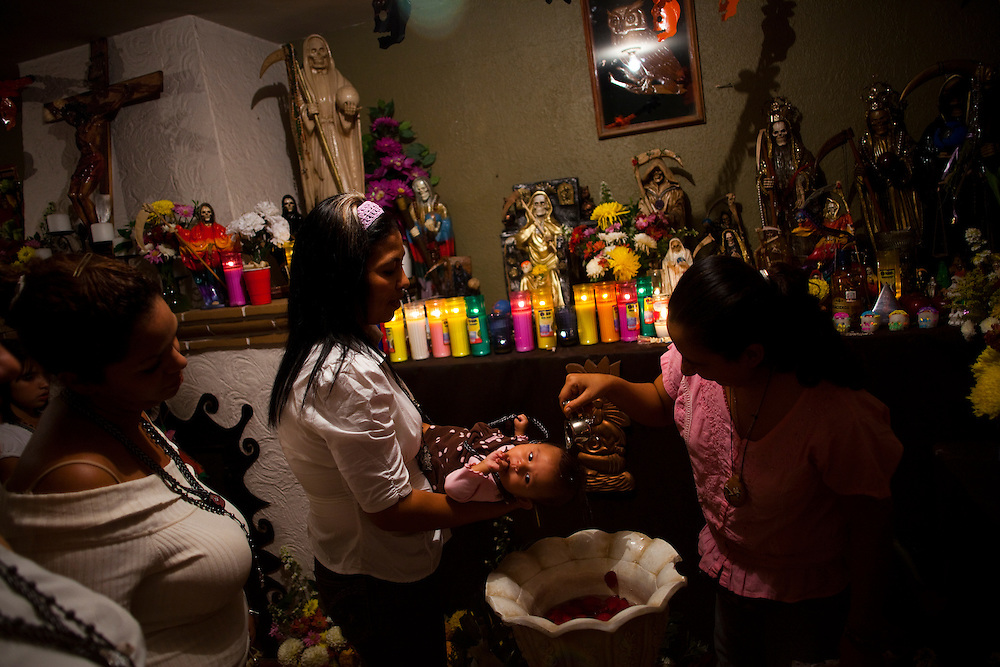 A young baby gets baptized in Ciudad Juarez at a shrine to La Santa Muerte, a skeleton folk saint that drinks tequila and smokes cigars.  It is believed that many criminals believe that La Santa Muerte protects them.