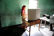 A woman casts her vote at a polling station during the second phase of voting in parliamentary elections April 23, 2009 in the Muslim dominated town of Mukalmua in the stare of Assam, India. Polling took place amid tight security after several acts of militant violence in recent days.