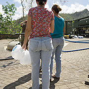OCTOBER 25 - UTUADO, PUERTO RICO - <br /> Residents line up to fill containers with potable water at a station next to the Lago Dos Bocas in Utuado. Troops from Fort Bragg, NC, are using a water filtration system to purify the liquid.<br /> (Photo by Angel Valentin/Freelance)