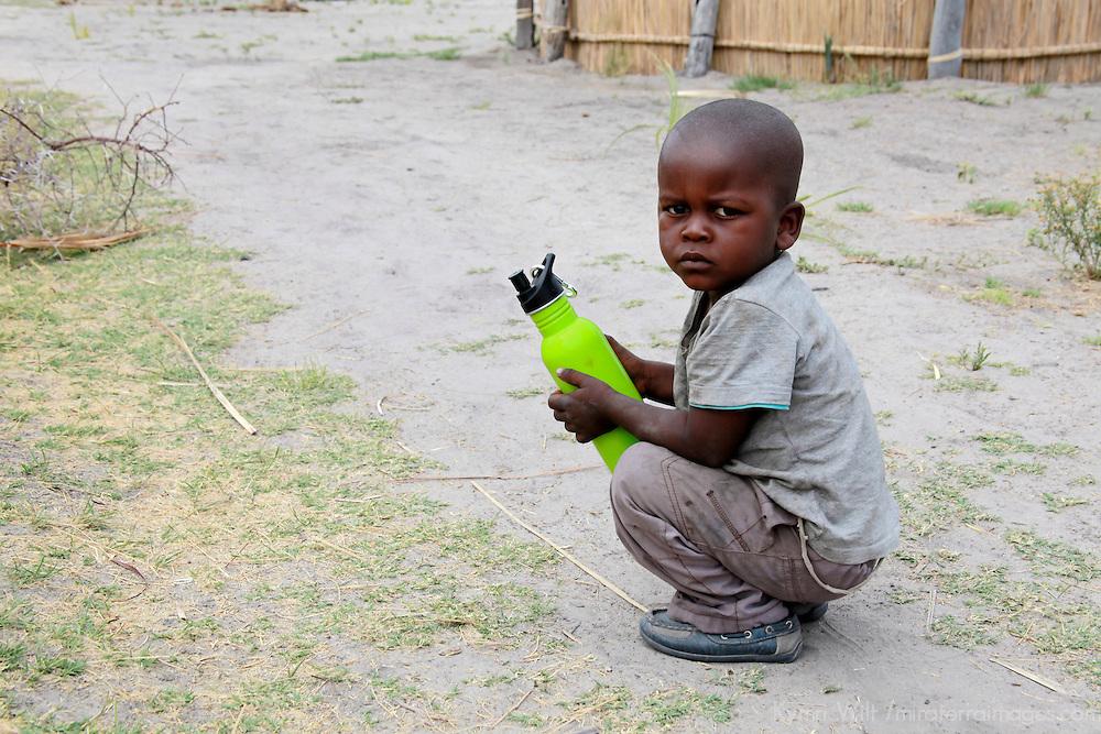 Africa, Botswana, Okavango Delta. A young boy growing up in an Okavango village holds a water bottle.