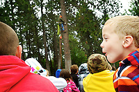 Braedon Pearce, 6, gets excited about Sammy Boyd, with All Seasons Tree Service, climbing a pine tree on the playground at Fernan Elementary during a CDA4Kids presentation Thursday.