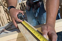 Man measuring half constructed wall with tape measure