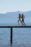 Women running along pier in front of mountains side view