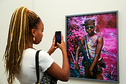 "© Licensed to London News Pictures. 15/05/2019. London, UK. A visitor takes a photograph of Richard Mosse's ""Rebel, Rebel, 2011"" photograph at the preview of Photo London 2019 at Somerset House, the largest photography event. The annual event in its fifth year, showcases the work of over 100 of the world's leading galleries from 21 different countries. The fair opens at Somerset House on 196 May and runs until 19 May 2019.  Photo credit: Dinendra Haria/LNP"