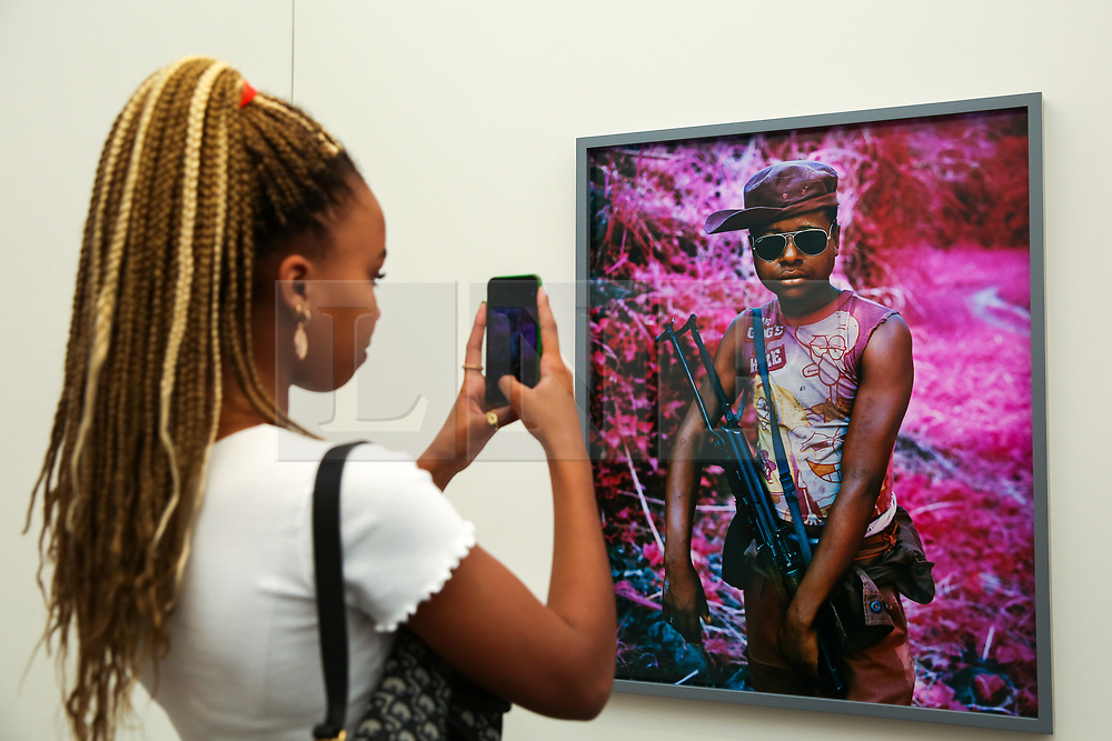 """© Licensed to London News Pictures. 15/05/2019. London, UK. A visitor takes a photograph of Richard Mosse's """"Rebel, Rebel, 2011"""" photograph at the preview of Photo London 2019 at Somerset House, the largest photography event. The annual event in its fifth year, showcases the work of over 100 of the world's leading galleries from 21 different countries. The fair opens at Somerset House on 196 May and runs until 19 May 2019.  Photo credit: Dinendra Haria/LNP"""
