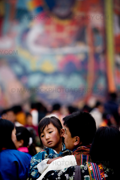 A young girl peers over her father's shoulder as they queue to get blessed by monks at the unveiling of the Thangka (religious mural) of Guru Rinpoche in the final event of the Paro festival at Rinpung dzong, Paro..Commonly described as the last Himalayan Shangrila, Bhutan is a country of unique serenity, harmony, and beauty. Nestled between India, China, and Tibet, this independent country whose name translates as 'the Land of the Thunder Dragon' has for the past 300 years  proactively followed a policy of isolation and cultural protection. Travel in and out of the country is strictly regulated, and the impact of outside influences on the local culture is carefully monitored. Spirituality is an important aspect of Bhutanese culture, with Buddhism being interlinked with everyday life. Gross National Happiness (GNH), as opposed to GNP/GDP, forms the cornerstone of its development strategy which focuses on a holistic development strategy that complements its cultural and Buddhist spiritual values.