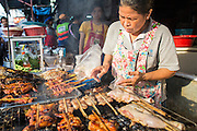 "26 SEPTEMBER 2012 - BANGKOK, THAILAND:  A street vendor grills chicken in Khlong Toey Market in Bangkok. Khlong Toey (also called Khlong Toei) Market is one of the largest ""wet markets"" in Thailand. The market is located in the midst of one of Bangkok's largest slum areas and close to the city's original deep water port. Thousands of people live in the neighboring slum area. Thousands more shop in the sprawling market for fresh fruits and vegetables as well meat, fish and poultry.    PHOTO BY JACK KURTZ"