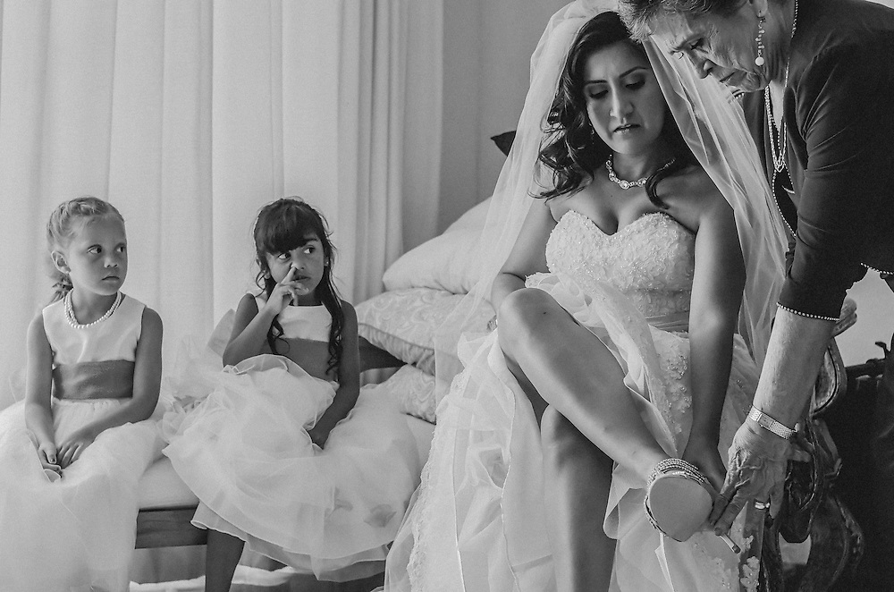 A mesmerized flower girl giving her undivided attention to the bride during the getting ready. Photo by: Juan Carlos Calderón