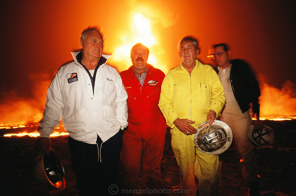 In March, 1991, heads of the three Texas oil well fire fighting companies made their first trip to Kuwait to survey the damage of the burning oil fields set ablaze by retreating Iraqi troops in February. Here in the Al Burgan field in mid afternoon, it was as dark as a moonless night due to the heavy thick smoke. The only light came from the more than 300 flaming oil wells and the truck headlights. It was raining soot and unburned oil. It was estimated that 5 or 6 million barrels of oil were being lost every day in this field alone. Huge oil lakes were forming. The men in the photo are: Boots Hansen (white jacket, Boots and Coots), Raymond Henry (Red Adair Company, red coveralls), Joe Bowden (Wildwell Control, yellow coveralls), and Larry Flak (oil well fire coordinator, black jacket)