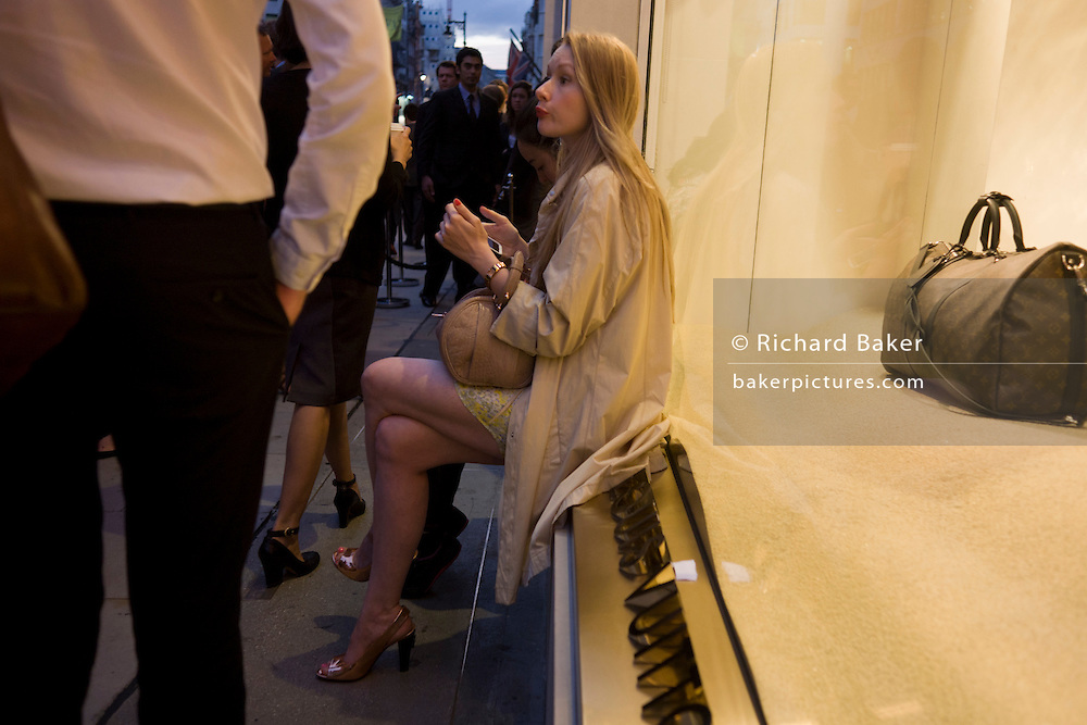Woman sits making calls outside the Louis Vuitton shop in London's Bond Street during Vogue's Fashion's Night Out festival in the streets of the West End. Sitting on the ledge of Louis Vuitton's shop, she sits cross-legged holding her smartphone as crowds pass-by during this busy period of the capital's fashion festival. One of the brand's esteemed bags is seen in the window display and the company logo is written across the ledge.