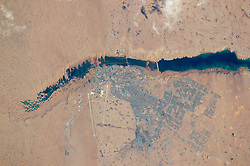 An astronaut aboard the International Space Station (ISS) put his or her earth-observation training to work in recognizing an unusual river that vanishes in a sand field well before it reaches the sea. The Hamra River (As Saquia al Hamra in Arabic) ends about 15 kilometers (9 miles) from the Atlantic Ocean in a dark blue lake. The river has cut into the landscape, making low cliffs on both sides. The river has its source in the mountains 300 kilometers (185 miles) inland, and it provides a persistent water supply for El Aaiún, the biggest city in Western Sahara. One of the most sparsely populated countries in the world, Western Sahara has a population of nearly half a million people; nearly 40 percent of them live in El Aaiún.<br /> The photograph was taken with the most powerful lens aboard the space station, and city blocks are easily detected in the gray cityscape. Even the white landing-marker lines on the airfield runways are visible, showing that the astronaut perfectly synchronized the camera's view-finder with the moving target. This allowed for one the best ground resolutions that can be achieved from the ISS: close to 3 meters per pixel.<br /> Small horn-shaped dunes are visible at the top left of the top image. The horns of these crescent dunes point south in the direction of dune movement. Sand from the dunes falls down the cliffs, making a spiky shoreline at the west end of the lake, and the dune field effectively prevents the river from reaching the sea. The dunes also restrict the westward expansion of the town. But scattered developments occupy an ancient delta of the river (top right) on more stable ground, where darker patches still indicate prior courses of the river.<br /> Related Image<br /> NASA Earth Observatory (2014, June 30) Desert Coast - Morocco, Western Sahara.<br /> Astronaut photograph ISS046-E-46013 was acquired on February 21, 2016, with a Nikon D4 digital camera using an 1150 millimeter lens, and is provided by the ISS Crew Earth Ob