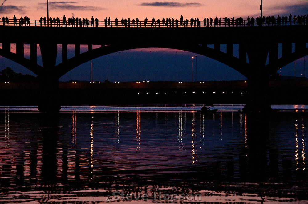Austinites line the Congress Avenue Bridge at sunset to watch the evening bat emergence, Austin, Texas, August 19, 2012.   The Ann W. Richards Congress Avenue Bridge houses the world's largest urban population of Mexican Free-tailed Bats.