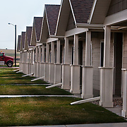 "Rows of brand new prefab houses along the highway on the outskirts of Watford City, North Dakota.  The oil boom has brought unprecedented prosperity to little towns like Watford City, N.D. (population 1,744), it has also exacerbated problems in housing, infrastructure and traffic...Williston (""Kuwait on the Prairie""), Watford City and their neighboring towns in North Dakota sit atop the biggest lake of oil to be discovered in North America since Alaska's Prudhoe Bay in 1968. ..There are too many unfilled jobs and not enough empty beds to accommodate the masses of people looking for work in the oil boom, man camps have sprung up throughout the formerly idyllic  prairie. They are dormitory-style buildings, FEMA trailers, or RV's, and a temporary solution to housing workers but are straining utilities and stretching towns emergency services."