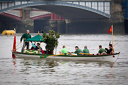 © Licensed to London News Pictures. 06/01/2013. London, UK. A member of the 'Bankside Mummers' dressed as 'the Holly Man' waves to onlookers as he is ferried along the Thames during the annual 'Twelfth Night' Celebration in London today (06/01/13). The tradition, a pagan celebration of the new year and the end if Christmas, takes place every year at Bankside outside the Globe Theatre and sees the actors of the Bankside Mummers perform for the public. Photo credit: Matt Cetti-Roberts/LNP
