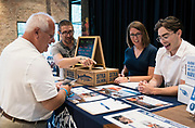 """Sitka Salmon Shares employees talk with attendees at the """"Garver Gourmet"""" at the newly opened Garver Feed Mill event space in Madison, Wisconsin, Saturday, Sept. 7, 2019."""