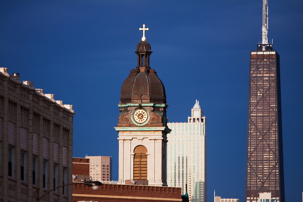Evening storms have passed, bathing the steeple at St. John Cantius church in glorious sunshine with the John Hancock building standing in the background.