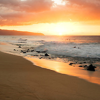 surfer on shore in distance on Oahu's North Shore at sunset