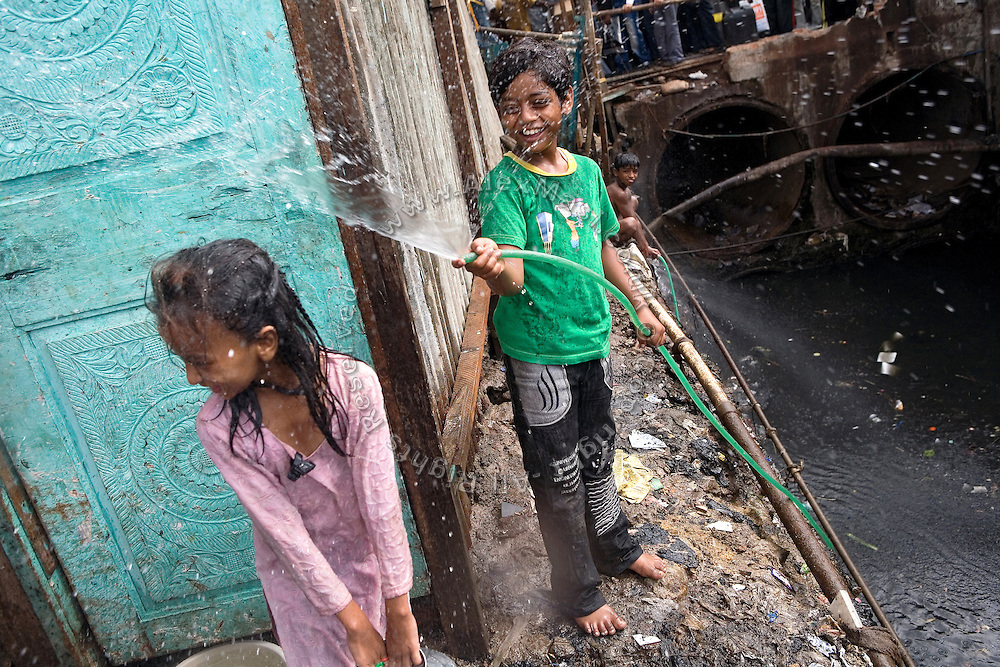 Azharuddin Ismail, 10, the child actor playing the role of 'young Salim', the brother of Jamal, protagonist of Slumdog Millionaire, the famous movie winner of 8 Oscar Academy Awards in December 2008, is playing with a water pump near a drain in the slum where he still lives with his family next to the train station of Bandra (East), Mumbai, India. Various promises were made to lift the two young actors (Azharuddin Ismail and Rubina Ali) from poverty and slum-life but as of the end of May 2009 anything is yet to happen. Rubina's house was recently demolished with no notice as it lay on land owned by the Maharashtra train authorities and she is now permanently living with her uncle's family in a home a stone-throw away in the same slum. Azharuddin's home too was demolished in the past two weeks, as it happens every year in his case, because the concrete walls were preventing local authorities to clear a drain passing right behind it. As usual, his father is looking into restoring the walls as soon as the work on the drain has been completed.