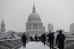 © Licensed to London News Pictures. 23/02/2017. LONDON, UK. Morning commuters cross Millennium Bridge during a heavy rain shower and windy weather as Storm Doris hits London and the south of England.  Photo credit: Vickie Flores/LNP