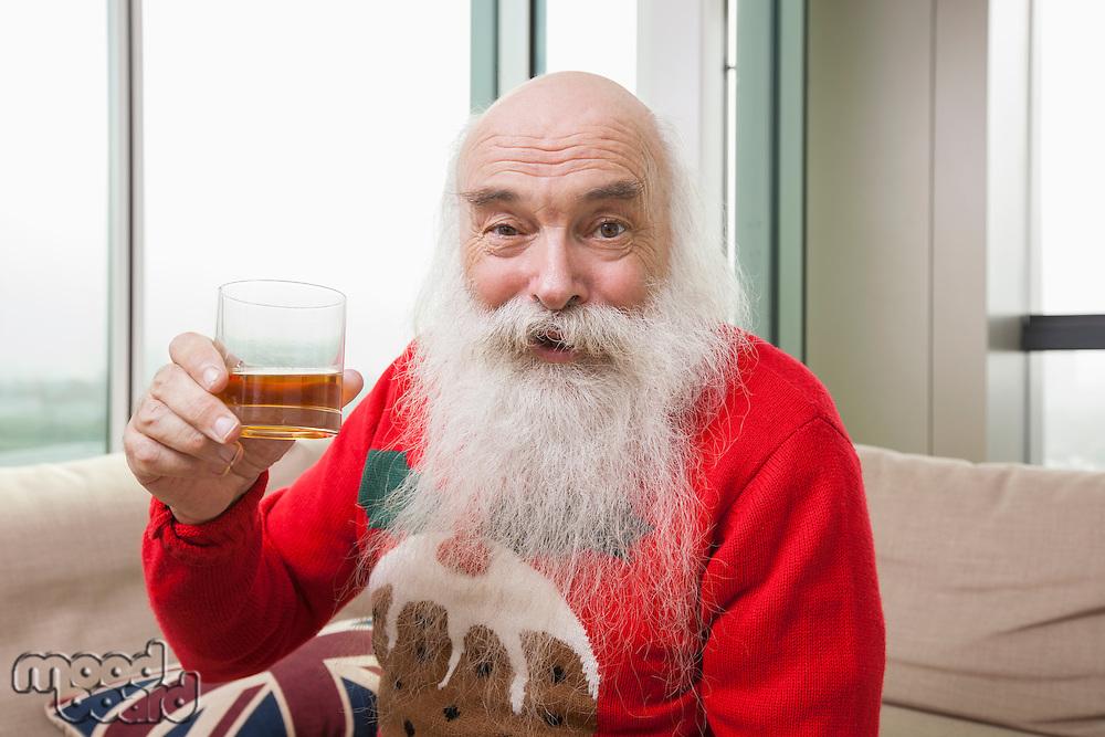 Portrait of senior man holding beer glass in living room