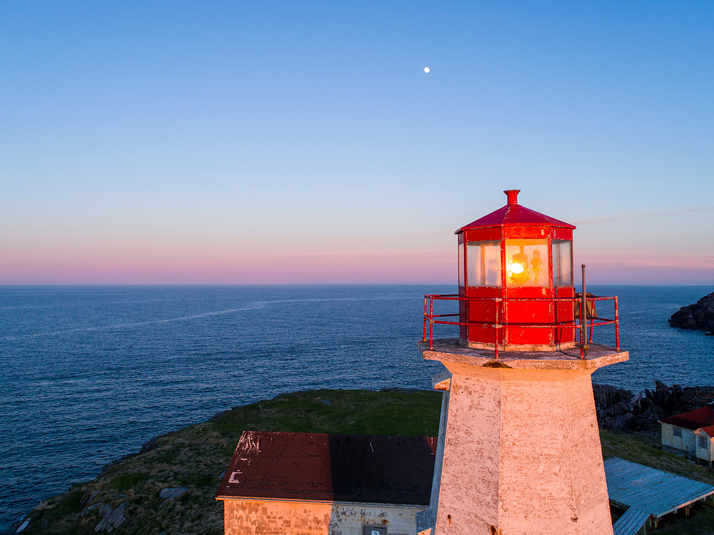 Canada, Nova Scotia, Aerial view of moonrise behind St. Paul Island Lighthouse in Cabot Strait at sunset on summer evening