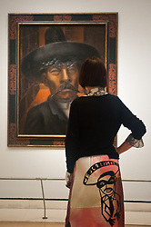 """Mexico: A Revolution in Art opens at the Royal Academy of Arts.<br /> A woman wears a skirt reading """"Mejico Lindo"""" and stands next to work by David Alfaro Siqueiros at the exhibition """"Mexico: A Revolution in Art, 1910 - 1940"""" which opens at the Royal Academy of Arts on the 6th of July. The show features over 120 paintings and photographs and examines the intense period of artistic creativity that took place in Mexico at the beginning of the 20th century,<br /> London, United Kingdom,<br /> Tuesday, 2nd July 2013<br /> Picture by Piero Cruciatti / i-Images"""