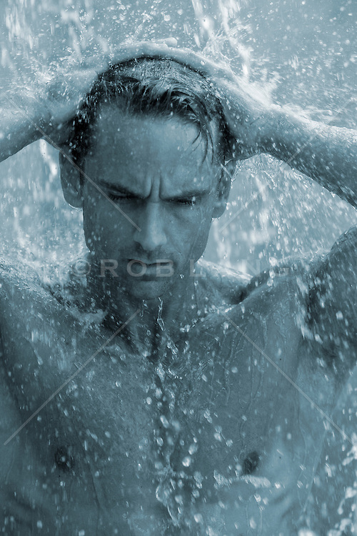 man under a waterfall in a swimming pool