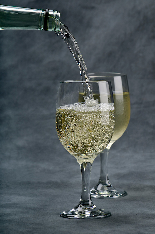 White wine being poured into crystal cups  on gray background.