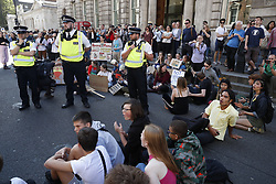 © Licensed to London News Pictures. 20/09/2019. London, UK. Young activists taking part in the Global Climate Strike demonstration sit down in the road near Trafalgar Square. Thousands of similar actions are taking place all over the UK and the rest of the world. Photo credit: Peter Macdiarmid/LNP