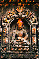 A small buddha carving with dye and paint on a neighborhood stupa in Patan.