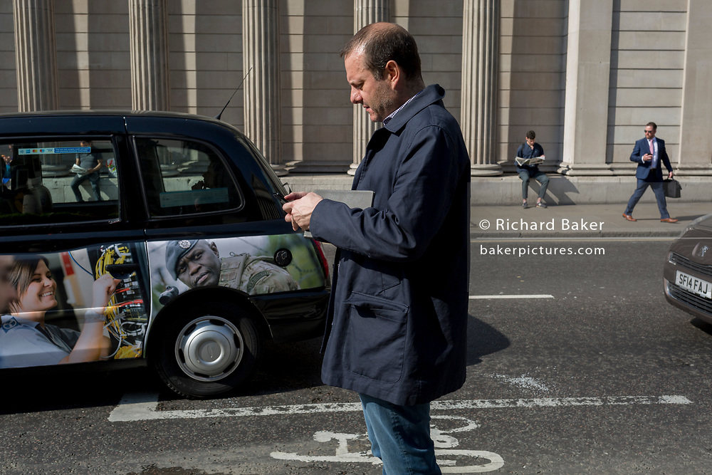 A man checks his messages opposite the Bank of England on Threadneedle Street in the City of London, the capital's financial district also known as the Square Mile, on 6th April 2017, in London, England.