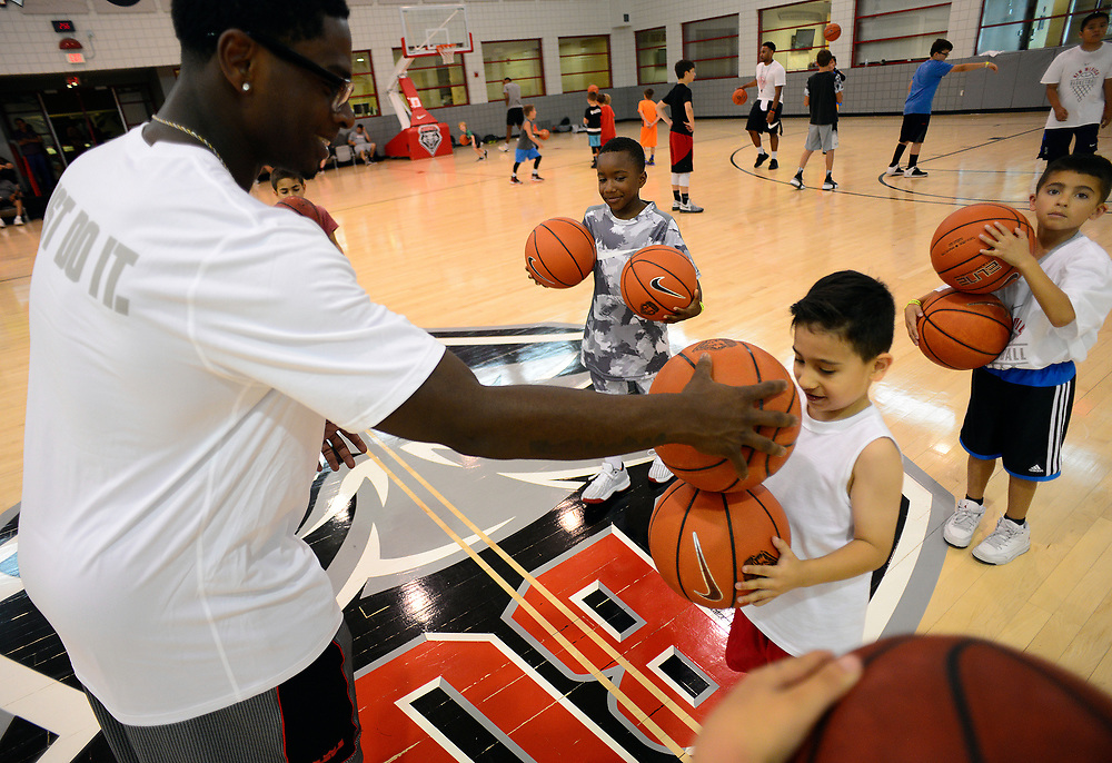 apl0604517a/SPORTS/pierre-louis/JOURNAL 060517<br /> Former UNM Lobo guard Jamal Fenton,, left , teaches ball handling to 6 year-old C.J. Ortega,, during the UNM Basketball Camp for Kids  .Photographed  on Monday June  5,  2017. .Adolphe Pierre-Louis/JOURNAL