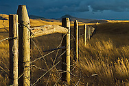 The setting sun illuminates a fence on ranching land in Montana.