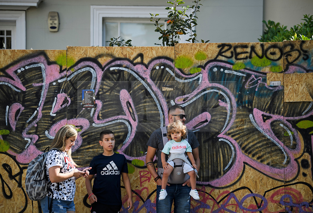 © Licensed to London News Pictures. 23/08/2019. London, UK. A family stands in front of a residential property boarded up as preparations begin in Notting Hill, West London ahead of the 2018 Notting Hill Carnival which starts this weekend. Warm weather is expected over the bank holiday weekend with carnival attracting over 1 million people to the capital. Photo credit: Ben Cawthra/LNP