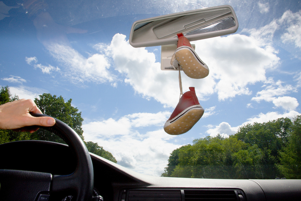 Mother driving with baby shoes hanging from rear view  mirror