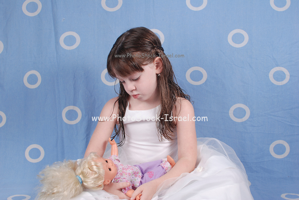 Girl of 5 in white dress plays with a doll