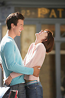 Laughing couple embracing in front of shop