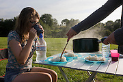 A 15 year-old teenage girl is sips tea whilst being served steaming rice in a field whilst on a family camping holiday.
